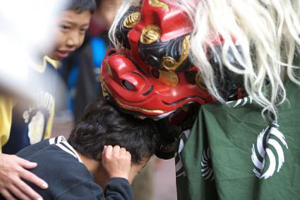 お正月 獅子舞に頭をかじられる子ども
