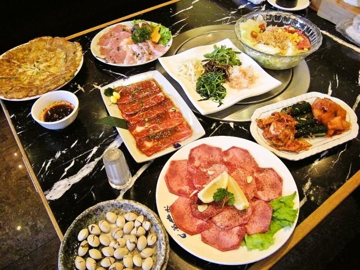 テーブルいっぱいに並べたお肉やサラダ、おつまみなど