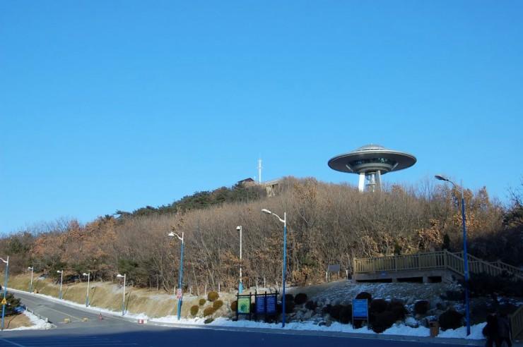 車で行ける頂上付近。道沿いには大きな鐘も展示されている。右側の木製の階段で展望へ向かう
