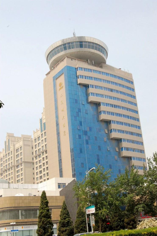 青い壁面と最上階の円盤型レストランが特徴のホテル外観