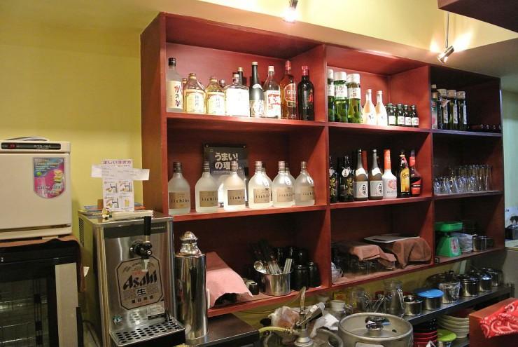 1階カウター席奥にはお酒が並ぶ棚