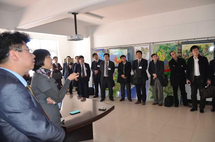 訪問先で熱心に説明を聞くビジネスツアーの参加者たち