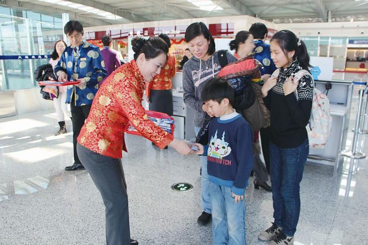 中国民族衣装姿のスタッフから記念品を受け取る乗客