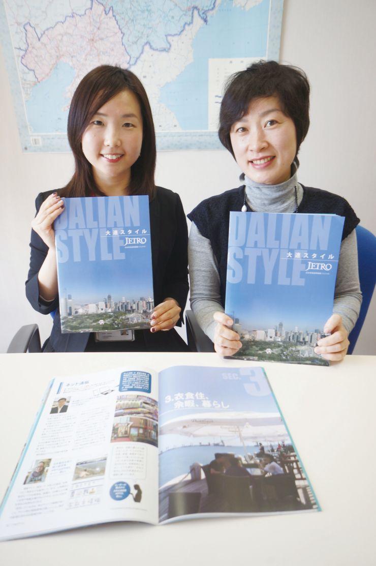 「大連スタイル」を手にする編集担当の森詩織さん(左)と呉冬梅さん