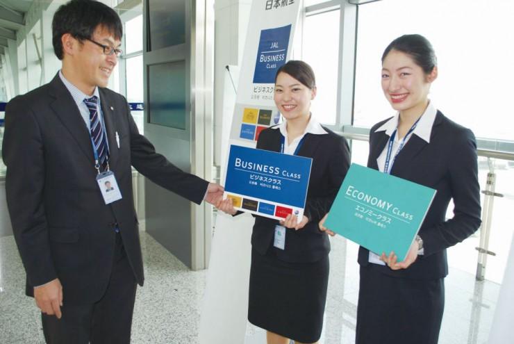 搭乗口で日本航空大連支店の社員から指導を受ける栄久庵さん(中)と門口さん(右)