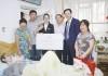 訪問先の家族と記念写真に収まるホテル・ニッコー大連のスタッフたち